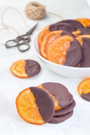 Homemade candied sliced oranges covered with chocolate, making sweet gifts, vertical