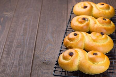 Traditional Swedish and scandinavian Christmas saffron buns Lussekatter on a cooling tray, brown wooden backgtound, horizontal, copy space Zdjęcie Seryjne - 138358146