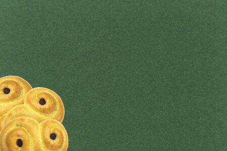 Traditional Swedish and scandinavian Christmas saffron buns Lussekatter on a green background, three in the corner, horizontal,  copy space