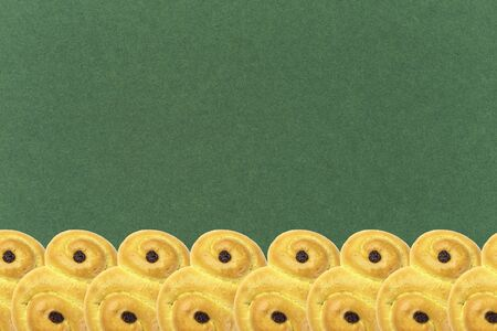 Traditional Swedish and scandinavian Christmas saffron buns Lussekatter on a green background, horizontal in a row, copy space Zdjęcie Seryjne