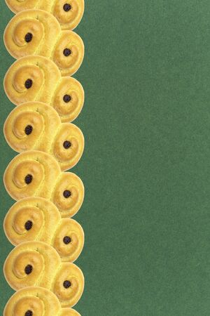 Traditional Swedish and scandinavian Christmas saffron buns Lussekatter on a green background, vertical in a row, copy space