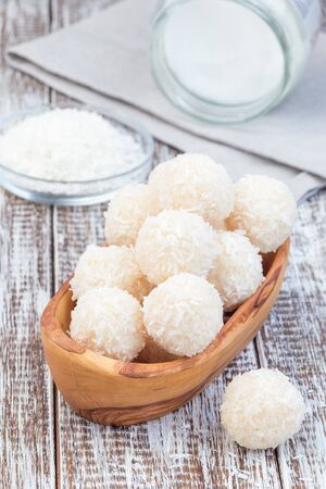 Homemade healthy raw paleo energy balls with shredded coconut, almond flour, coconut butter and sweetener in wooden bowl, vertical Zdjęcie Seryjne