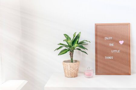 Scandinavian style home interior with a white table or workspace, green palm in pot, and pegboard with inspiring phrase, minimalistic concept, sun rays from the window, horizontal, copy space
