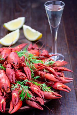 Crayfishes on a plate served with dill, lemon and glass of schnapps, dark wooden background, vertical