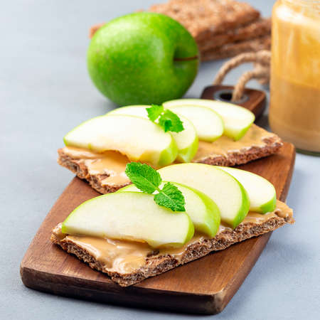 Healthy sandwich with low carb whole grain cracker, green apple slices and peanut butter, on a wooden board, square format
