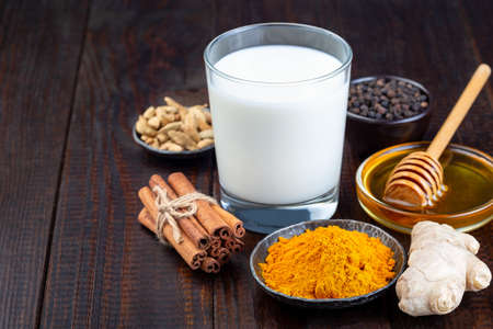 Ingredients for turmeric moon milk on a wooden background, horizontal, copy space