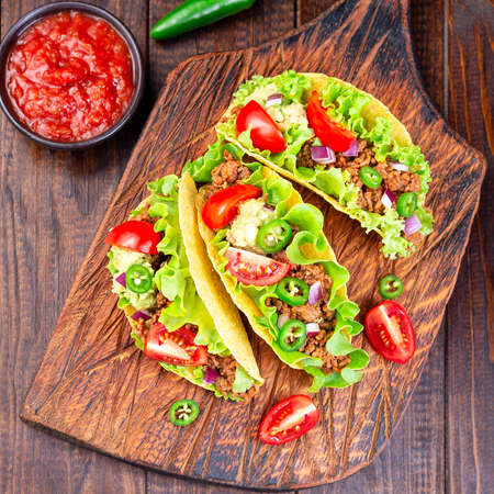 Taco with ground beef meat, mashed avocado, tomato, lettuce, red onion, jalapeno pepper, square, top view