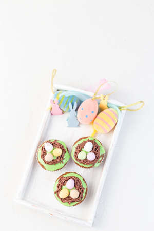Easter carrot cake muffins with cream cheese frosting and chocolate eggs, on a white wooden tray with Easter eggs, bunnies and feathers, vertical, copy space, top view