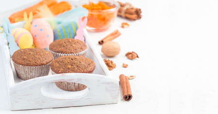 Banner with carrot cake and walnut muffins on a white wooden tray with Easter eggs, bunnies and feathers, horizontal, copy space Stok Fotoğraf