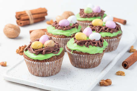 Carrot cake muffins with cream cheese frosting and Easter chocolate eggs, on a white plate, horizontal