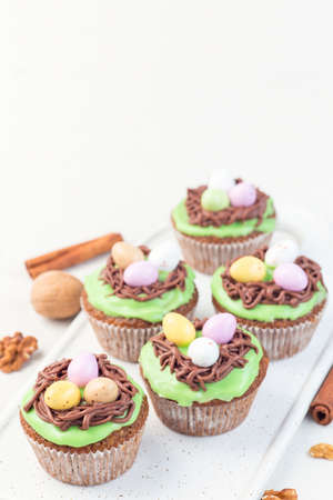 Carrot cake muffins with cream cheese frosting and Easter chocolate eggs, on a white plate, vertical, copy space Stok Fotoğraf