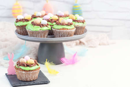 Easter carrot cake muffins with cream cheese frosting and chocolate eggs, on a gray cake stand, horizontal, copy space