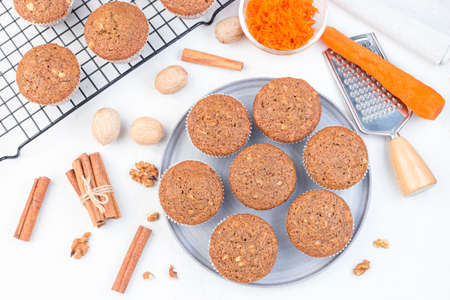 Carrot cake muffins with walnuts on a gray plate and cooling rack, horizontal, top view Stok Fotoğraf
