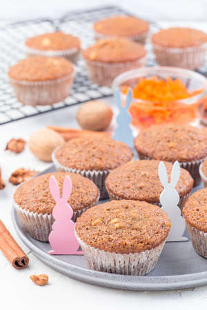 Carrot cake muffins with walnuts on a gray plate and cooling rack, decorated with wooden Easter bunnies, vertical Stok Fotoğraf