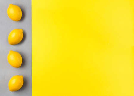 Yellow paper and gray concrete texture, fresh lemons on gray background, colors of year 2021, horizontal, copy  space 免版税图像