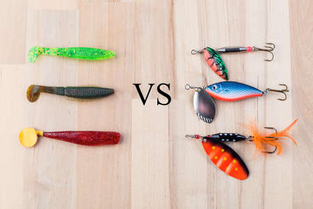 Various fishing accessories, silicone jig vs metal spoon, and  on a wooden background, 23 november 2020, Gothenburg, Sweden