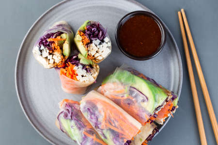 Vegetarian spring rolls with tofu and vegetables, cut and served with sauce, on a gray plate, horizontal, top view, closeup 免版税图像