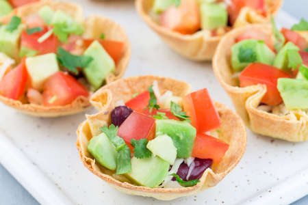 Veggie taco cups with corn tortilla, black beans, tomatoes, avocado and cheese, on a white plate, horizontal, closeup