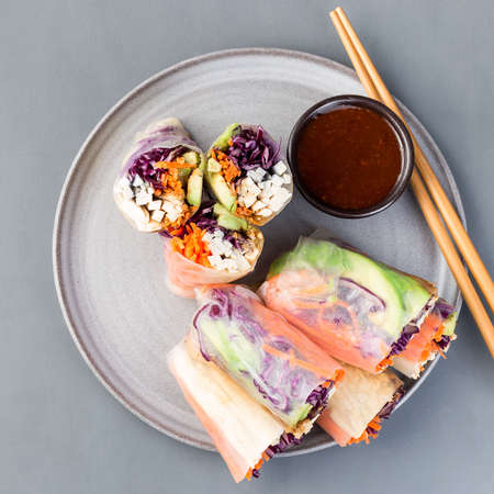 Vegetarian spring rolls with tofu and vegetables, cut and served with sauce, on a gray plate, square format, top view