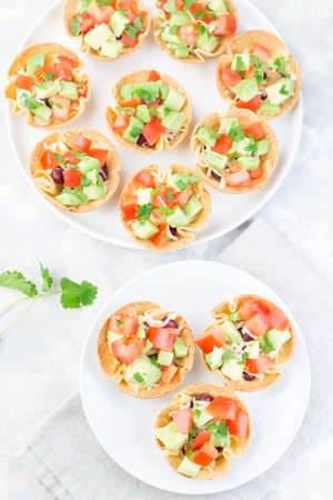 Taco cups with corn tortilla, black beans, tomatoes, avocado and cheese,  vertical, top view