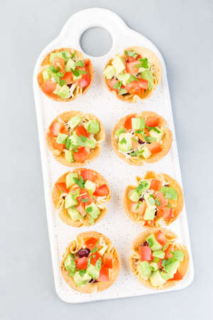 Veggie taco cups with corn tortilla, black beans, tomatoes, avocado and cheese,  vertical, top view, closeup