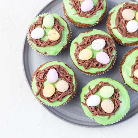 Carrot cupcakes with cream cheese frosting and Easter chocolate eggs, on a gray plate, top view, square format 免版税图像