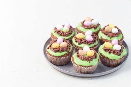 Carrot cupcakes with cream cheese frosting and Easter chocolate eggs, on a gray plate, horizontal, copy space 免版税图像