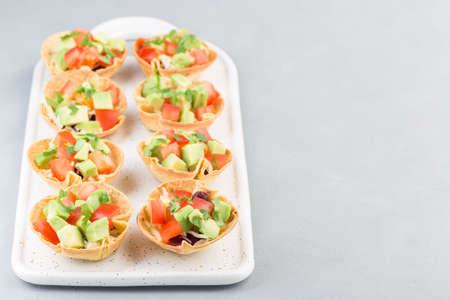 Veggie taco cups with corn tortilla, black beans, tomatoes, avocado and cheese,   horizontal, copy space 免版税图像