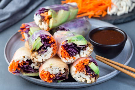 Vegetarian spring rolls with tofu and vegetables, cut and served with sauce, on a gray plate, horizontal