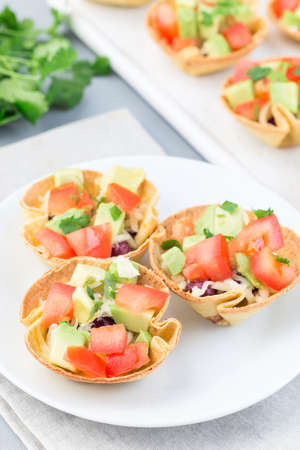 Veggie taco cups with corn tortilla, black beans, tomatoes, avocado and cheese,  vertical 免版税图像