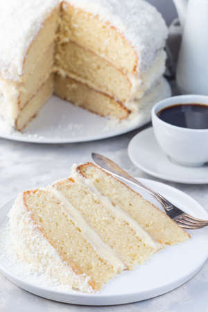 Piece of homemade coconut cake with cream cheese frosting and coconut flakes decoration, on a white plate, vertical