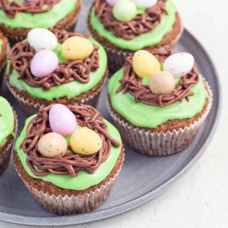 Carrot cupcakes with cream cheese frosting and Easter chocolate eggs, on a gray plate, square format