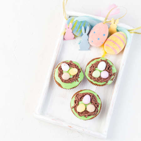 Homemade carrot cupcakes with cream cheese frosting and Easter decoration, on a white wooden tray, top view, square format