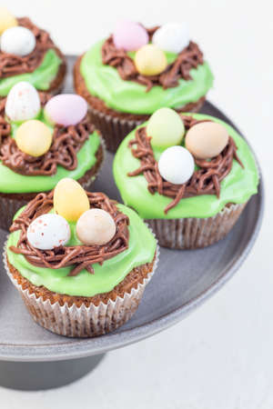Carrot cupcakes with cream cheese frosting and Easter chocolate eggs, on a gray cake stand, vertical
