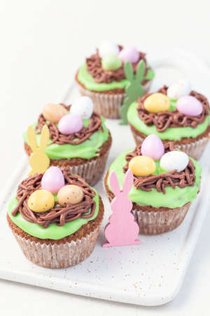 Homemade carrot cupcakes with cream cheese frosting and Easter chocolate eggs, wooden bunny decor, on a white plate, vertical
