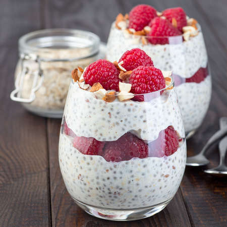 Overnight oats with chia and flax seeds, garnished with raspberry and almond, on a wooden background, square format 免版税图像