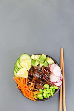 Vegetarian tofu poke bowl with brown basmati rice and vegetables, vertical, top view, copy  space 免版税图像