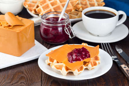 Homemade waffles with norwegian brown cheese and lingon jam, on a wooden background, horizontal