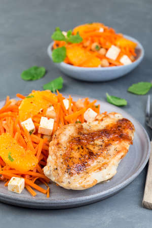 Roasted chicken breast with carrot, chickpeas, feta cheese salad, on a gray plate, vertical 免版税图像
