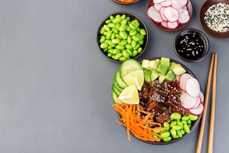 Vegetarian tofu poke bowl with brown basmati rice and vegetables, horizontal, top view, copy  space 免版税图像