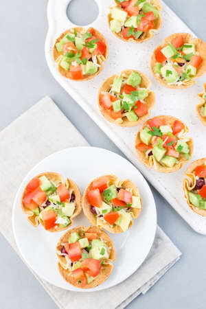 Taco cups with corn tortilla, black beans, tomatoes, avocado and cheese, on a white plate, vertical, top view