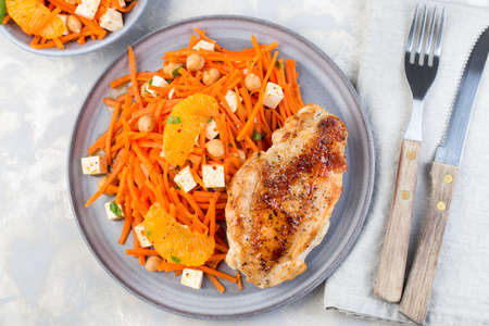Roasted chicken breast with carrot, chickpeas, feta cheese salad, on a gray plate, horizontal, top view 免版税图像