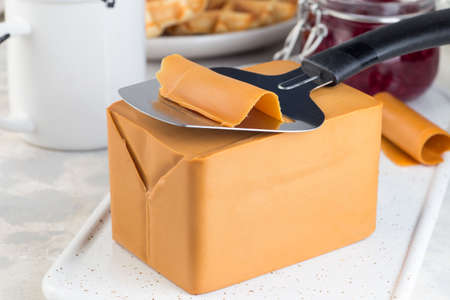 Piece of Norwegian brown cheese with cheese slicer, horizontal,  closeup