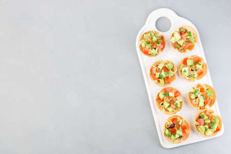 Taco cups with corn tortilla, black beans, tomatoes, avocado and cheese,  horizontal, top view, copy space
