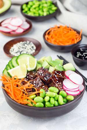 Vegetarian tofu poke bowl with brown basmati rice and vegetables,  vertical