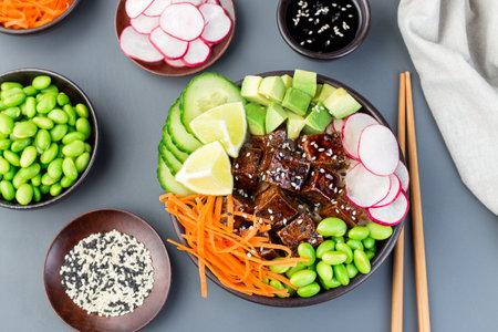 Vegetarian tofu poke bowl with brown basmati rice and vegetables, horizontal,  top view