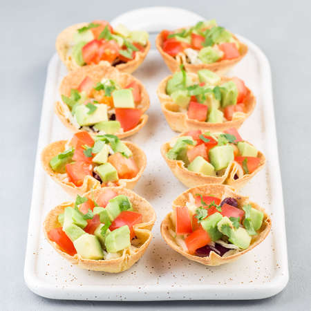 Veggie taco cups with corn tortilla, black beans, tomatoes, avocado and cheese, square format