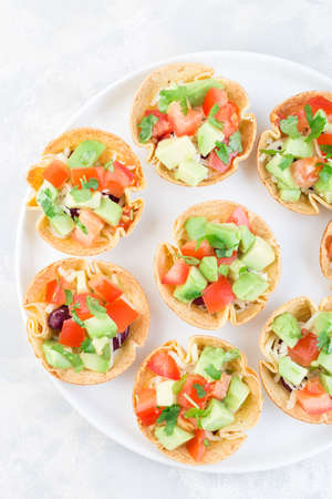 Veggie taco cups with corn tortilla, black beans, tomatoes, avocado and cheese, on a white plate, vertical, top view, closeup