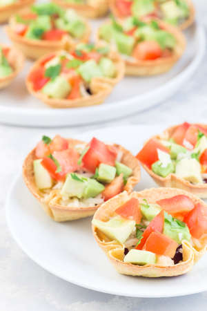 Veggie taco caps with corn tortilla, black beans, tomatoes, avocado and cheese, on a white plate, vertical 免版税图像