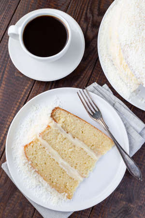 Piece of coconut cake with cream cheese frosting and coconut flakes decoration, on white plate, vertical, top view, closeup